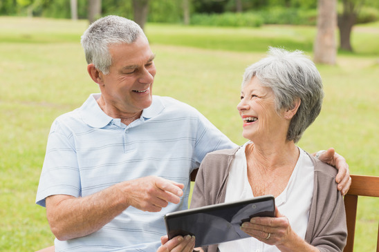 Cheerful senior woman and man using digital tablet on bench at the park